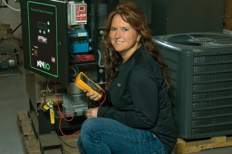 An Energy Systems Technology student monitors an HVAC device.